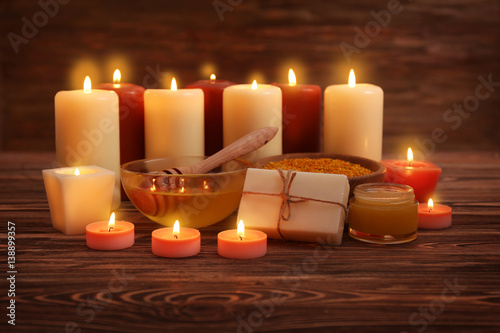 Photo Beautiful composition of alight candles and honey treatments on wooden table