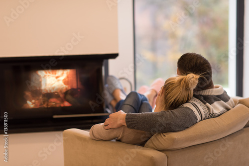 Cuadros en Lienzo Young couple  in front of fireplace