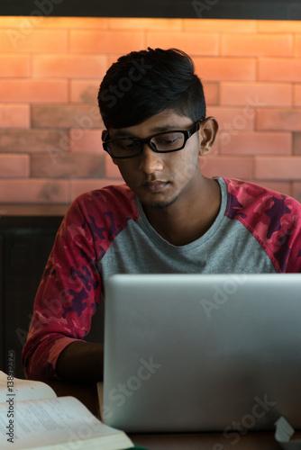 Fototapeta indian teenage male drinking coffee doing homework at cafe obraz na płótnie