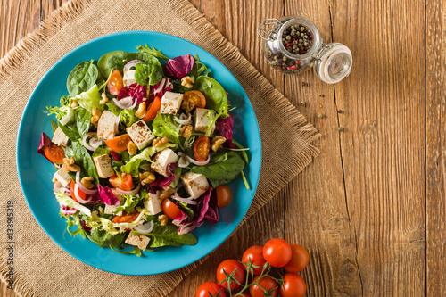 wysmienita-salatka-z-tofu-pomidorow-i-orzechow-wloskich-podana-na-niebieskim-talerzu
