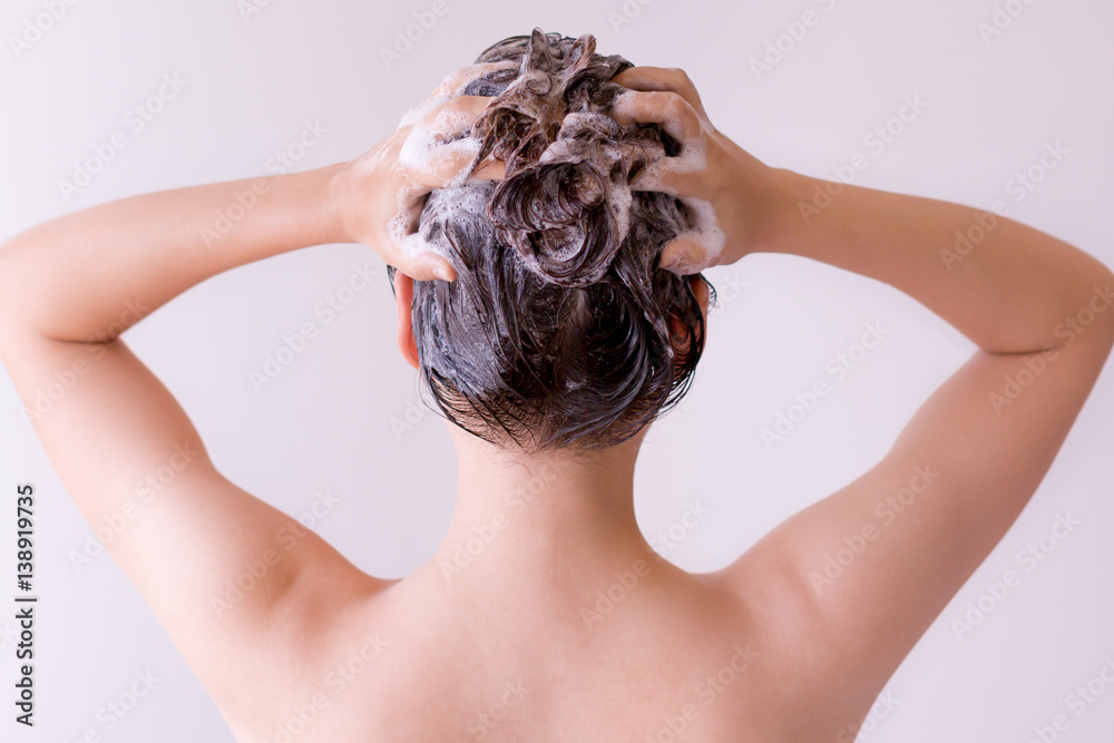 Fototapeta Sexy model massaging shampoo into her hair, closeup profile from the back