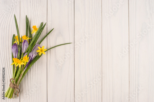 Poster Muguet de mai Daffodils and crocuses on the old white wooden table.