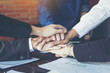 business people join hand while meeting in office
