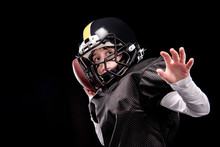 Little Boy American Football Player In Uniform Throwing Ball On Black