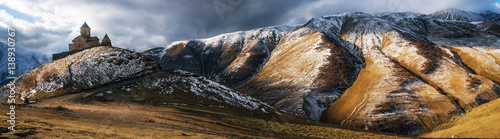 Fotobehang Grijze traf. Panoramic view of Caucasus mountains, Gergeti Trinity church Tsminda Sameba against the stormy cloudy sky in a morning, landmark of Georgia