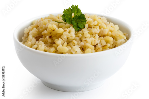 Cooked bulgur wheat with green parsley in white ceramic bowl isolated on white Fototapet