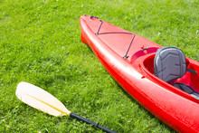 Red Kayak And Yellow Row Lays On The Green Grass And Waiting For The Journey