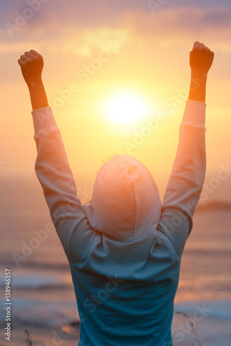Rear view of motivated woman celebrating workout goals towards the sun. Morning healthy training success.