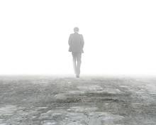 Man Walking In Mist On Dirty Concrete Floor