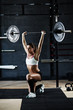 Crossfit motivation: beautiful fit sportswoman pausing in champion pose performing overhead barbell lunges in dark modern gym