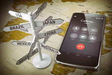 Global Communication, Calls Abroad, Roaming Concept. Mobile Phone And Signboard With Different Directions On Map Of The World.