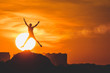 Leinwandbild Motiv Human silhouette jumping at solar disk sunny summer sunset drive holidays and vacations