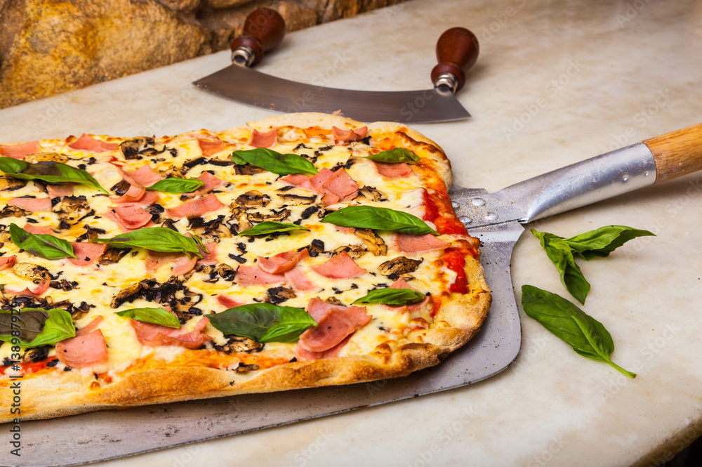 Hot pizza on a paddle, straight from the oven.