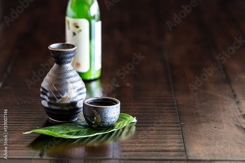 Japanese sake set and a bottle of sake on the rustic wood table.