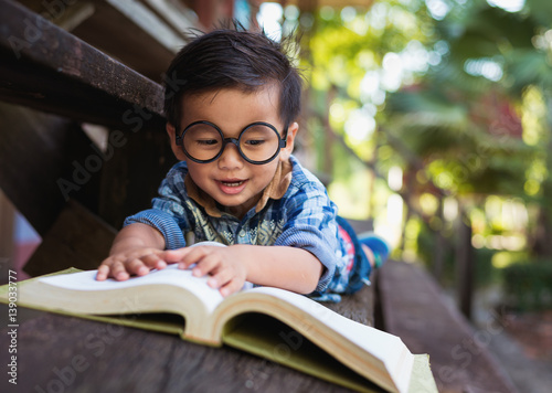 chlopiec-w-okularach-z-duza-ksiazka-w-ogrodzie