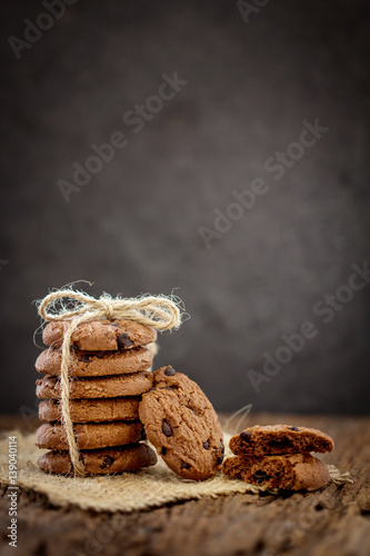 Fotobehang Koekjes Still life of Close up stacked chocolate chip cookies on napkin with rustic background