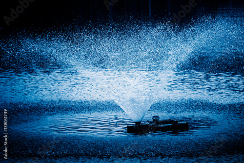 Fotografie, Obraz  Aerator,a device for water oxygenation in an artificial pond for breeding fish,blue toned