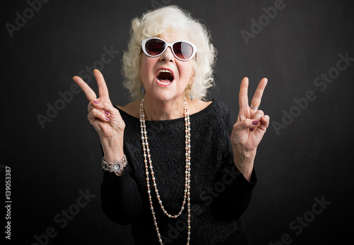 Fotografia  Cool grandmother showing peace sign