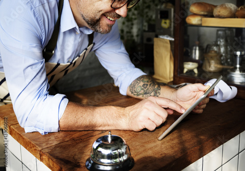 Tuinposter koffiebar Adult Man Using Tablet in Bakery Shop