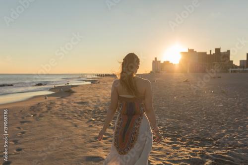 mloda-kobieta-idzie-na-coney-island-beach-o-zachodzie-slonca-nowy-jork-usa