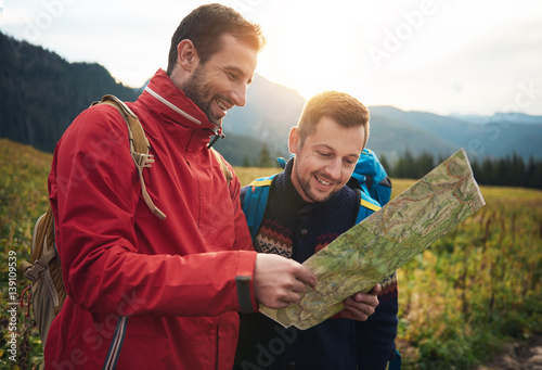 Fotografia  Smiling hikers reading a trail map in the wilderness