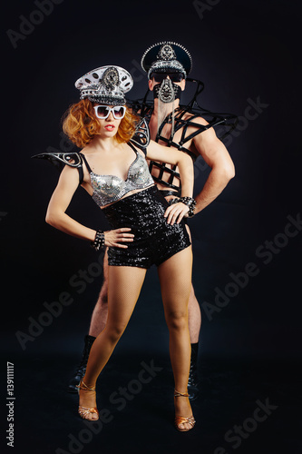 Montage in der Fensternische Karneval Studio portrait of Dancer Couple in black sexy costume mask and cap with metal elements on black background