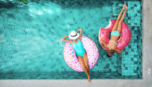People Relaxing On Inflatable Ring In Pool