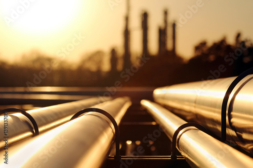 Fototapeta golden sunset in crude oil refinery with pipeline system obraz
