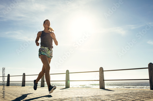 Fitness young woman jogging along the beach