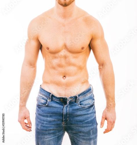 Plakat Mięśniowy młody człowiek jest ubranym cajgi Odizolowywających na białym tle.