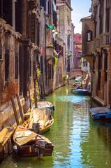 Fototapeta na wymiar Traditional narrow canal with gondolas in Venice, Italy
