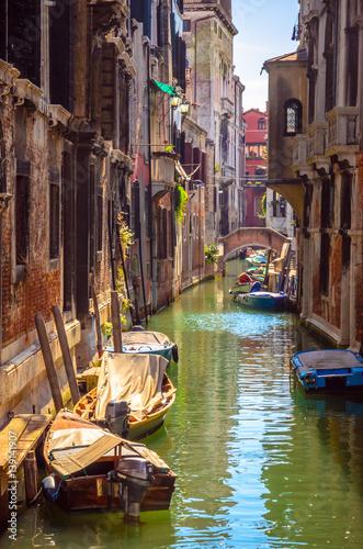 Fototapeta Traditional narrow canal with gondolas in Venice, Italy