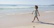 Female walking along the shore of the beach raising her hands up. Tarifa beach. Provincia Cadiz. Spain.