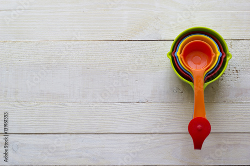 Fotografia, Obraz  Colorful measuring spoons for kitchen on a white wooden background