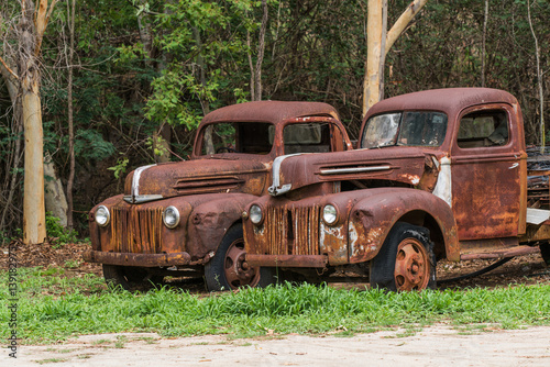 Foto  Two rusty old Ford trucks abandoned