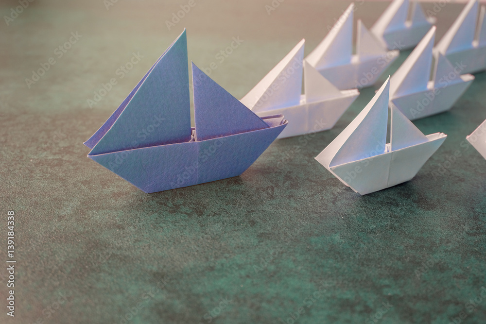 Fototapeta Origami paper big sailboat with small sailboats, leadership, marketing concept, social media influencers, HR recruiter, standing out concept