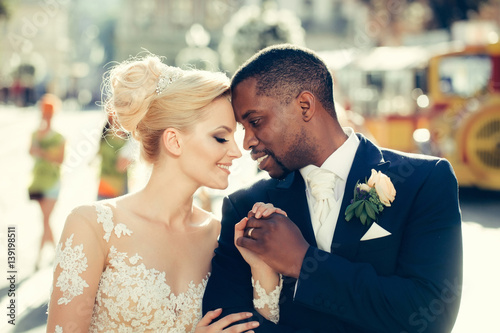 Photo Loving couple of cute bride and african American groom