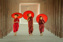 Myanmar The Three Novice Walking On The Pagoda And Holding Red Umbrella In Mandalay,Myanmar.