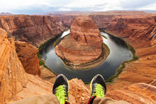 Legs Of Traveler Man Sitting On The Background Of The Canyon Horseshoe Bend, Arizona, USA. Travel Concept, Scenic View