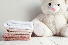 Stack Of Spa Towels On White Wooden Table With White Soft Toy Bear On Background. Childrens Washing Concept