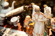 Antique Porcelain Woman And Other Figurines And Crockery At The Flea Market. Old Ceramic Girl Statuette And China Tableware Collectibles At The Garage Sale