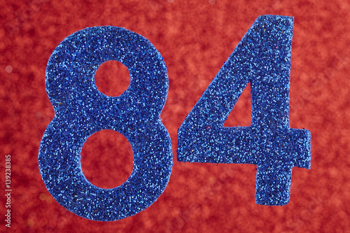 Fotografia  Number eighty-four blue color over a red background. Anniversary.