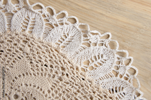 Fotografia, Obraz  Knitted homemade white lacy doily on wooden background.