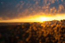 Abstract Bokeh Background, Sunset After Rain, Shining Raindrops On Window, Focus On City Buildings