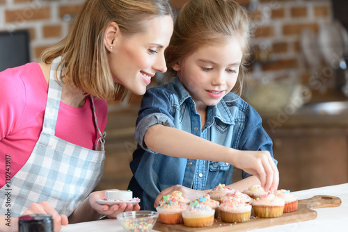 side view of daughter and mother decorating cupcakes with confetti Wallpaper Mural