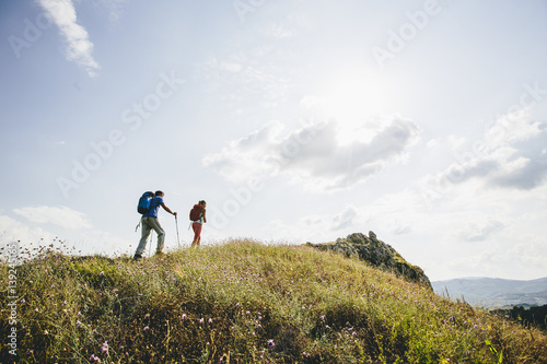 Fotografie, Obraz  Hikers with backpacks walking on top of a mountain and enjoy hiking