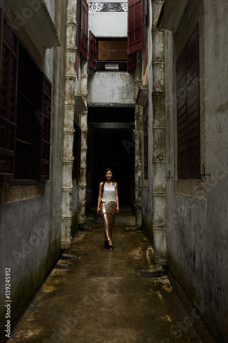 Narrow alley Young woman walking down narrow alley between buildings