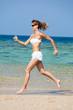 femme souriante en été qui court sur une belle plage