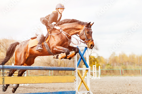 Foto Bay horse with rider girl jump over hurdle on show jumping competition
