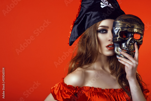 Fényképezés  Portrait of gorgeous sexy woman with provocative make-up in pirate costume hiding the half of her face behind skull mask
